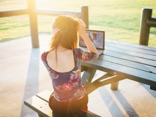 Imagen de una chica con una laptop en un parque