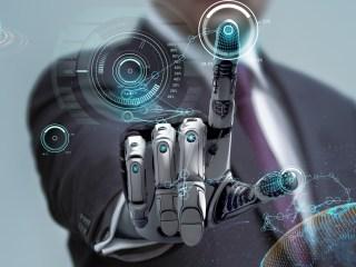 Las interfaces cerebro-máquina no son dispositivos nuevos ni proyectos del futuro. Hace tiempo que se estudian en medicina con el fin de paliar algunas enfermedades relacionadas con el sistema motor o de tipo neurológico. Los científicos llevan años investigando cómo realizar una comunicación efectiva entre un dispositivo digital y el cerebro. Pero cabe predecir que la iniciativa de Elon Musk pondrá en el candelero de la primera plana a esta tecnología. Los primeros ensayos de Neuralink con humanos cada vez están más cerca. Es la dirección que lleva la compañía. A mediados de 2019, Musk anunció que los ensayos de Neuralink con ratones y con primates ya eran una realidad. La startup apuntó en aquella fecha que el próximo año le tocaría el turno a los primeros humanos. No resulta sorprendente teniendo en cuenta el ritmo al que desarrollan sus investigaciones. Hay que recordar que la fundación de la empresa tuvo lugar en 2016. Musk ha declarado en más de una ocasión, y de forma clara, que el objetivo último de Neuralink es fusionar máquinas y humanos. Una suerte de simbiosis entre la tecnología, caracterizada en forma de inteligencia artificial, computación, y las personas. Pero aún queda para llegar a esos niveles. Por ahora, cabe esperar que los ensayos con humanos ayuden a mitigar los efectos de trastornos neurológicos. La idea es tratar a pacientes cuya movilidad se ha visto reducida, por ejemplo. Para hacerlo, los ensayos de Neuralink tendrán que introducir sobre el cráneo de los pacientes un dispositivo que se conecta al cerebro. En total son 3.072 electrodos, que se distribuyen en 96 hilos, cada uno de los cuales tiene que ser introducido en una región del cerebro. Estas estructuras intercambian información con un módulo externo, que se sitúa cerca de la oreja. Se trata de una técnica invasiva, que requiere cirugía. Para llevarla a cabo la compañía ha diseñado un robot capaz de instalar seis hilos de electrodos por minuto. Un impulso a las interfaces cerebrales 