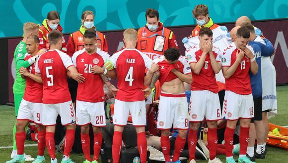 Jugadores de la selección Danesa cubren a su compañero de las cámaras
